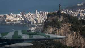 A F-5 fighter flies past the Christ the Redeemer statue while intercepting another aircraft, photographed through a window, during a Brazilian Air Force presentation for the press ahead of the Olympic games in Rio de Janeiro, Brazil, Thursday, July 14, 2016. (Felipe Dana/AP Photo)