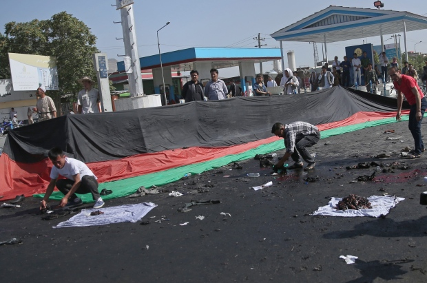 Afghans gather property, left behind by victims of a deadly explosion that struck a protest march by ethnic Hazaras, in Kabul, Afghanistan, Saturday, July 23, 2016. (AP / Massoud Hossaini)