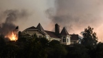 A wildfire burns close to a home near Sand Caynon and Placerita Caynon in Santa Clarita, Calif., Saturday, July 23, 2016. (AP / Ryan Babroff)
