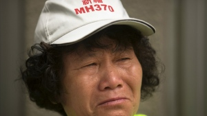 A woman wearing a hat reading 'Pray for MH370' cries as she stands outside the Ministry of Foreign Affairs in Beijing, China on Friday, July 29, 2016. (AP / Mark Schiefelbein)