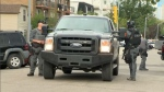 Members of the CPS tactical unit return to their vehicle following the arrests of two suspects in connection with a crime spree in Cochrane and Airdrie