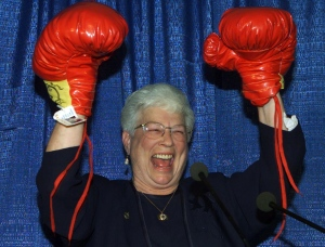 In this file photo, then-Conservative candidate for Saint John, Elsie Wayne, raises her hands after receiving a pair of boxing gloves from a man dressed in a blue Santa suit during her nomination meeting in Saint John, N.B. Monday Oct. 23, 2000. (THE CANADIAN PRESS/Jacques Boissinot)