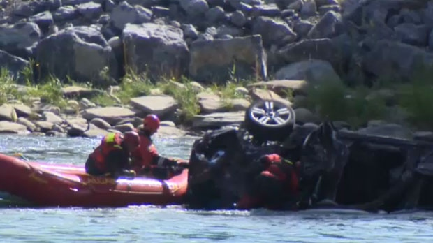 Members of the Calgary Fire Department aquatic rescue team search the overturned SUV in the Bow River