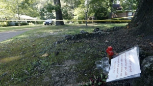 A verse of scripture, a cross, three candles and some faded flowers lay on a tree root across from the Durant, Miss., home of Sister Margaret Held and Sister Paula Merrill in Durant, Miss. on Friday, Aug. 26, 2016. (AP / Rogelio V. Solis)
