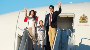 Prime Minister Justin Trudeau, his wife Sophie Gregoire, and daughter Ella-Grace wave as they board a government plane in Ottawa, Monday August 29, 2016. (THE CANADIAN PRESS/Adrian Wyld)