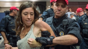 A demonstrator is taken away by a police officer after disrupting the National Energy Board public hearing into the proposed $15.7-billion Energy East pipeline project proposed by TransCanada, in Montreal, Monday, Aug. 29, 2016. (Paul Chiasson / THE CANADIAN PRESS)