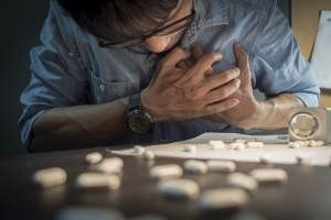 A man holds his chest next to a spilled bottle of pills in this file photo. (iStock.com / eggeeggjiew)