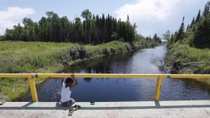 A boy from the Shoal Lake 40 First Nation sits on a bridge over a channel on on Thursday, June 25, 2015. (John Woods/THE CANADIAN PRESS)