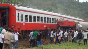 In this image made from video, people walk beside a derailed train carriage after an accident in Eseka, Cameroon, Friday, Oct. 21, 2016. (Equinox TV via AP)