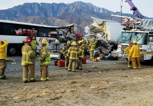 This photo provided by KMIR-TV shows the scene of crash between a tour bus and a semi-truck crashed on Interstate 10 near Desert Hot Springs, near Palm Springs, in California's Mojave Desert Sunday, Oct. 23, 2016. Multiple deaths and injuries were reported. (KMIR-TV via AP)
