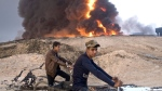 In this Sunday, Oct. 23, 2016 file photo, youths ride bicycles next to a burning oil well in Qayara, about 31 miles (50 km) south of Mosul, Iraq. (AP Photo/Marko Drobnjakovic, File)