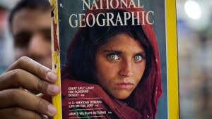 Pakistan's Inam Khan, owner of a book shop shows a copy of a magazine with the photograph of Afghan refugee woman Sharbat Gulla, on Oct. 26, 2016. (B.K. Bangash / AP)