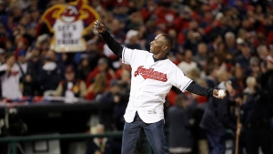 Former Cleveland Indians outfielder Kenny Lofton throws the ceremonial first pitch before Game 1 of the Major League Baseball World Series against the Chicago Cubs Tuesday, Oct. 25, 2016, in Cleveland. A longtime fan gave up his seat to Lofton on a delayed flight from Los Angeles to Cleveland so Lofton could arrive on time. (David J. Phillip/THE ASSOCIATED PRESS)