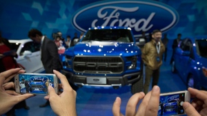 In this April 23, 2016, file photo, attendees take photos of a Ford F-150 Raptor pickup truck by smartphones at a promotional event for Ford ahead of the biennial Auto China car show in Beijing. Ford Motor Co. reports financial results Thursday, Oct. 27, 2016. (AP Photo/Mark Schiefelbein)