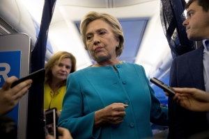 Democratic presidential candidate Hillary Clinton, accompanied by travelling press secretary Nick Merrill, right, and Director of Communications Jennifer Palmieri, left, takes a question from a member of the media aboard her campaign plane, Wednesday, Oct. 26, 2016, while travelling to Westchester. Clinton turns 69 today. (AP Photo/Andrew Harnik)