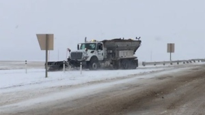 Road crews remove snow from the QEII Highway near the Crossfield overpass on Sunday afternoon