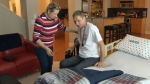 Dorota Doborowolski helps her husband Junasz into his temporary bed in the living room of their home