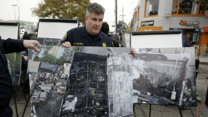 Alameda County Sheriff J.D. Nelson holds an aerial picture of a warehouse fire near the site Monday, Dec. 5, 2016, in Oakland, Calif. (AP / Marcio Jose Sanchez)