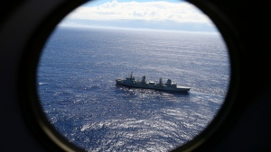 HMAS Success scans the southern Indian Ocean, near the coast of Western Australia, as a Royal New Zealand Air Force P3 Orion flies over, while searching for missing Malaysia Airlines Flight MH370 on March 31, 2014. (AP / Rob Griffith)