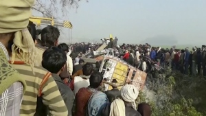 People gather at the site where a truck loaded with sand collided with a school bus in the northern Indian state of Uttar Pradesh on Thursday, Jan. 19, 2017. (KK Production)