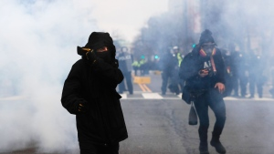 A protester shields his mouth and nose from gas fired by police during a demonstration after the inauguration of U.S. President Donald Trump in Washington on Friday, Jan. 20, 2017. (AP Photo/John Minchillo)