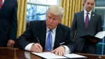 U.S. President Donald Trump signs an executive order to withdraw the U.S. from the 12-nation Trans-Pacific Partnership trade pact agreed to under the Obama administration, Monday, Jan. 23, 2017, in the Oval Office of the White House in Washington. (AP Photo/Evan Vucci)