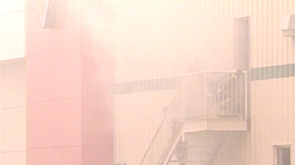 Fire crews were enveloped in the smoke as it pours from a door at the store.