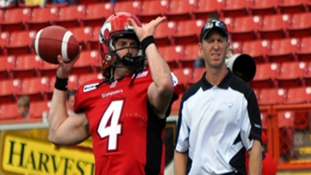 Stamps Offensive Coordinator (and former QB) Dave Dickenson watches quarterback Drew Tate warm up with his receivers.