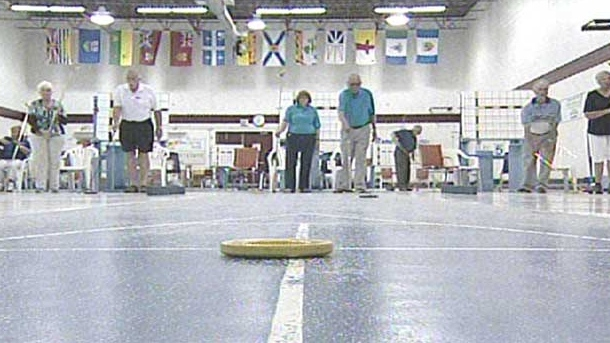 Members of the Foothills Shuffleboard Association practice pushing the biscuit at the curling club.