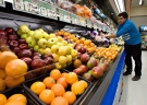 Grocery store owner Gilles Robin works on his fruits vegetable display in Breakeyville, Que. on Nov. 28, 2006. (Jacques Boissinot / THE CANADIAN PRESS)