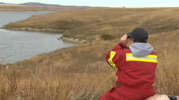 An emergency responder surveys the reservoir using binoculars